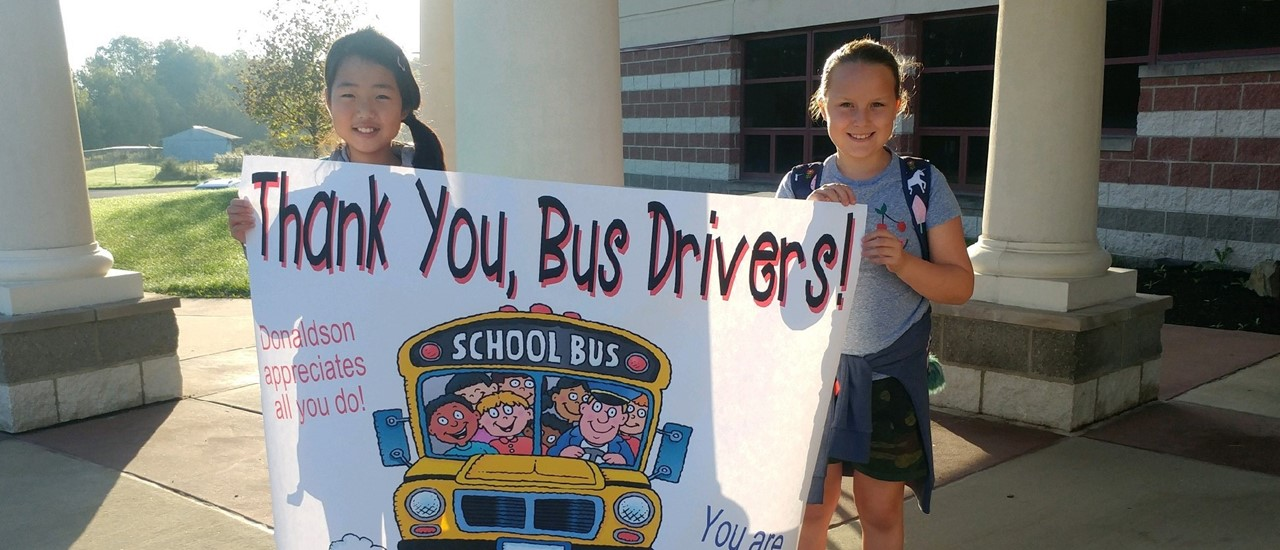 students with thank you banners